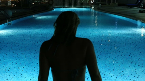 woman by pool at night